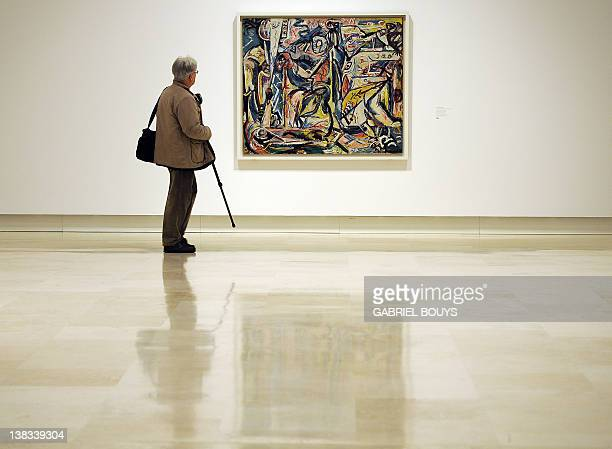 A journalist holding a monopod looks at 'Circumsision' by US artist Jackson Pollock belonging to the Guggenheim foundation as part as an exhibition...