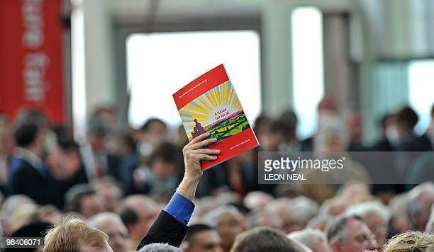 A journalist holds a copy of Labour's manifesto in the air as he waits to ask British Prime Minister and Labour Party leader Gordon Brown a question...