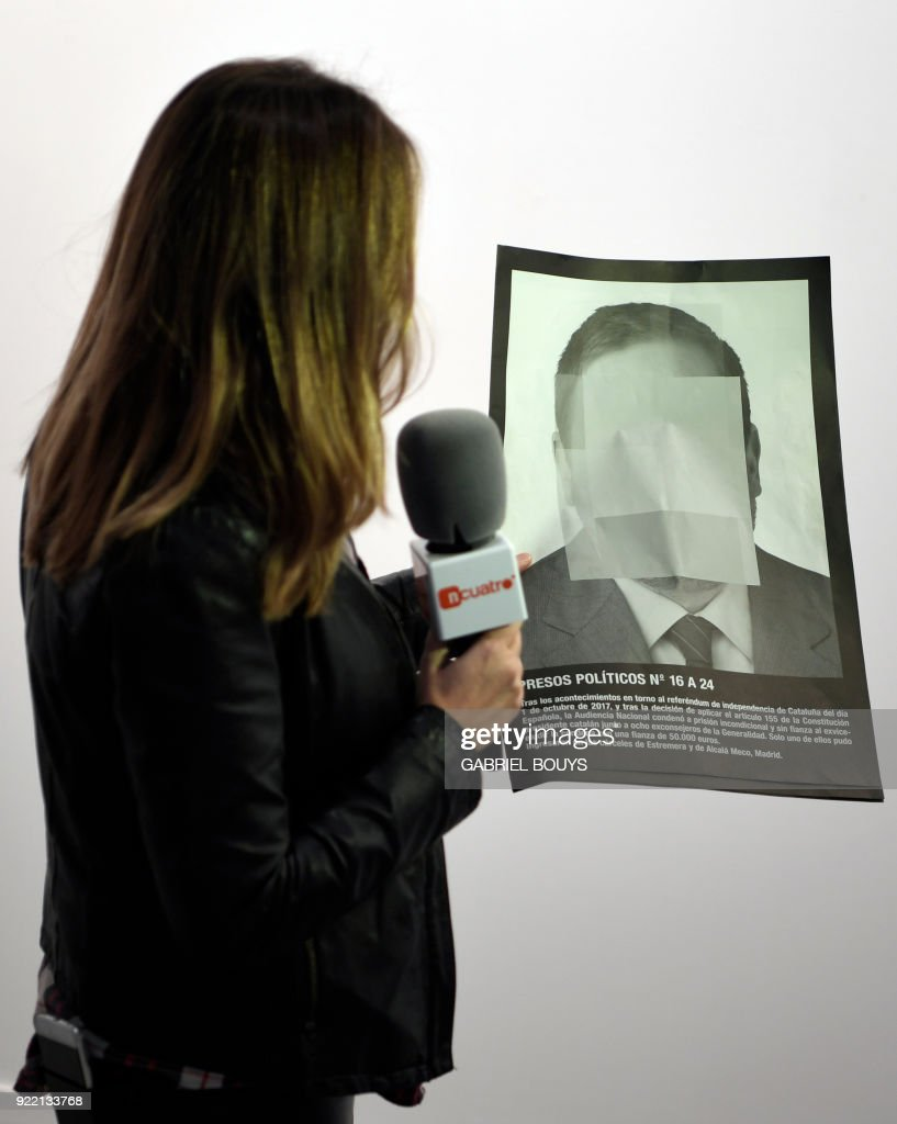 A journalist holds a photograph, part of the art-installation by Spanish artist Santiago Sierra 'Political prisoners of contemporary Spain' as she informs on its removal from ARCO art fair in Madrid on February 21, 2018. A photo exhibit by a Spanish artist known for his provocative stunts which depicts three jailed Catalan separatist leaders as 'political prisoners' was removed today from a major contemporary art fair in Madrid at the request of a government-funded body that operates the event venue. The dispute over the work by Madrid-born artist Santiago Sierra comes amid simmering tensions between Spain's central government in Madrid and pro-independence groups in Catalonia over their failed independence push. /