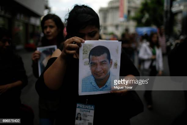 A journalist holds a portrait of killed journalist Armando Rodriguez Carreon 'El Choco' during a demonstration to end violence against journalists in...