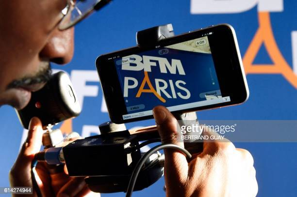 A journalist holds a shoulderpod a tripod mount adapter as the logo of BFM Paris is pictured on the display of a smartphone during a press conference...