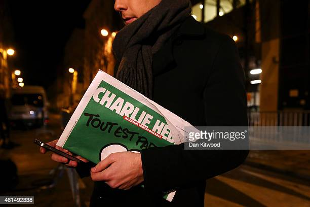 A journalist holds an early copy of a Charlie Hebdo magazine while delivering a news report outside the offices of Liberation Newspaper Group on...
