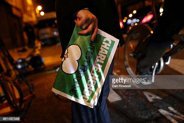 Journalist holds an early copy of a Charlie Hebdo magazine while delivering a news report outside the offices of Liberation Newspaper Group on...