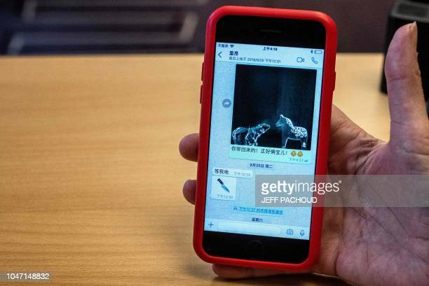 A journalist holds the mobile phone of Grace the wife of the missing Interpol president Meng Hongwey showing wath she says is the last message...