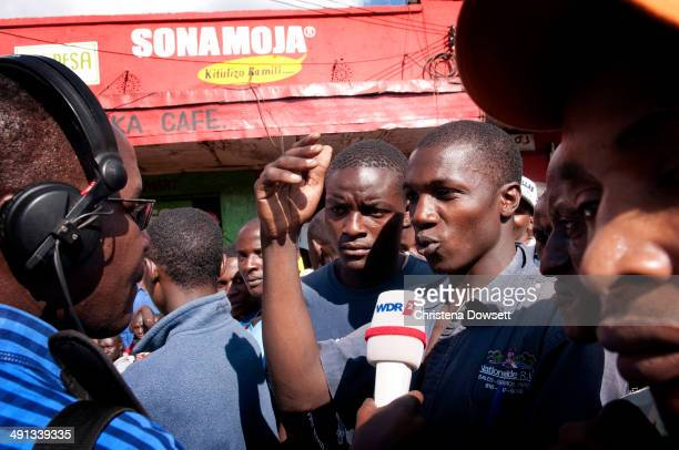 A journalist interviews a bystander after two improvised explosive devices went off in Gikomba market on May 16 2014 in Nairobi Kenya Two improvised...