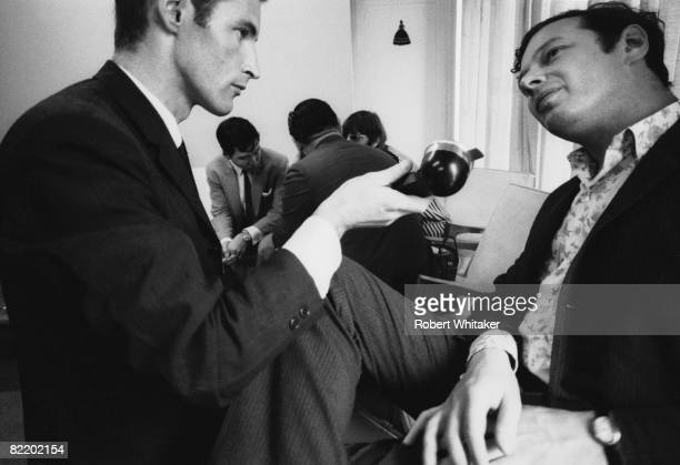A journalist interviews Beatles manager Brian Epstein in the VIP lounge at Kaitak Airport Hong Kong as the group waits for a connecting flight to...