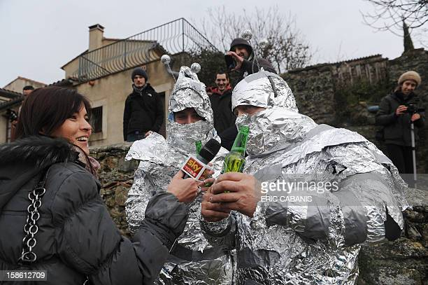 A TV journalist interviews men disguised in 'martians' on December 21 in the street of the French southwestern village of Bugarach near the 1231...