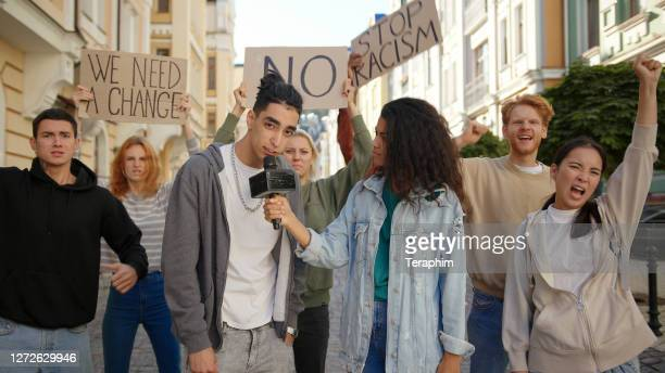 journalist interviews mixed race activist in front of multiracial protest mob - journalist stock pictures, royalty-free photos & images