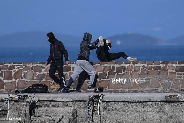 TOPSHOT A journalist is attacked by residents who are trying to prevent migrants from disembarking on the Greek island of Lesbos on March 1 2020 The...