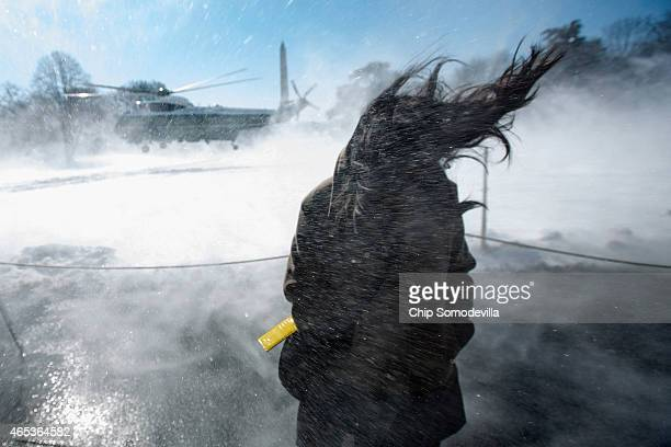 A journalist is blasted with snow blown by the Marine One presidential helicopter as it lifts off from the South Lawn of the White House with US...