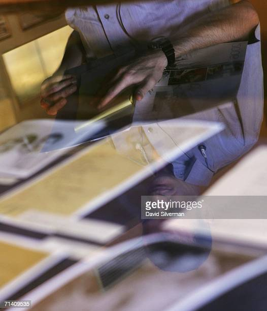 A journalist is reflected in the glass protecting letters and images made public by the Albert Einstein Archives at the Hebrew University July 10...