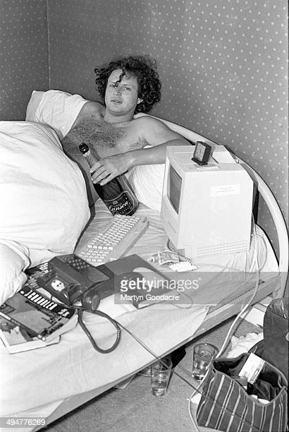 NME journalist James Brown lies in bed with an Apple Macintosh computer a bottle of champagne a phone and a Raymond Chandler novel London United...