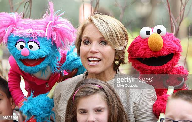 Journalist Katie Couric poses between two Sesame Street Muppets at the tree planting ceremony at Madison Square Park on April 8 2010 in New York City