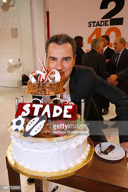 Journalist Laurent Luyat poses behind the Birthday Cake of the 'Stade 2' France 2 TV Chanel Sports Issue wich celebrates its 40th Birthday during the...