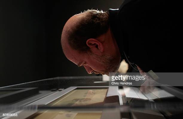 A journalist leans over to take a closer look at one of the Dead Sea Scrolls at the The Jewish Museum September 17 2008 in New York City The Dead Sea...