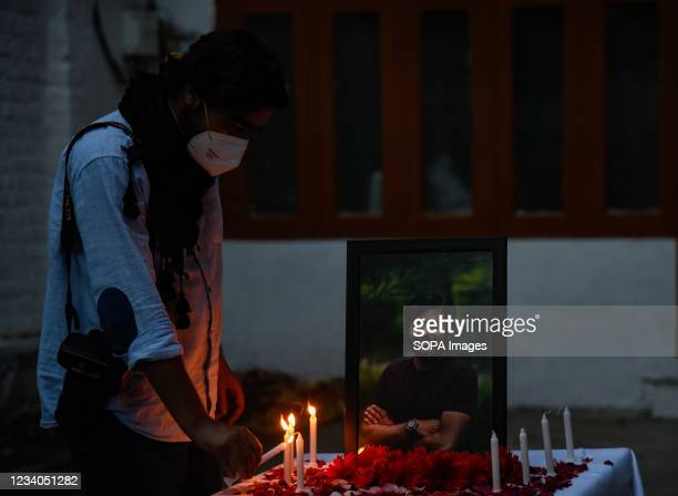 Journalist lights candles in front of a portrait of Danish Siddiqui during a candle light vigil in Srinagar. Reuters journalist Danish Siddiqui was...
