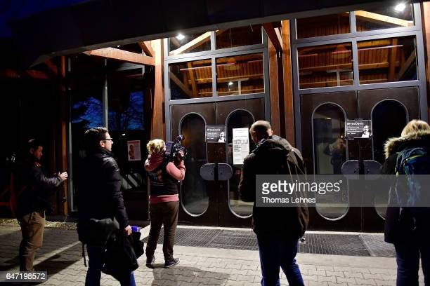 Journalist look at a sign for the arrested journalist Deniz Yuecel stick at the Festhalle Bad Rotenfels hall after a planned rally for expatriate...