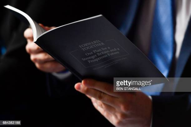 A journalist looks at a copy of the Conservative Party's general election manifesto at the launch event in Halifax in northern England on May 18 2017...
