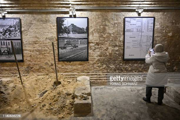 A journalist looks at a map an pictures of the area in an exhibition inside the entry hall leading to a tunnel formerly used to escape former East...