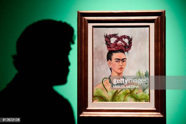 A journalist looks at a painting by Mexican artist Frida Kahlo entitled Self portrait with Braid during a press visit to her exhibition Oltre il mito...
