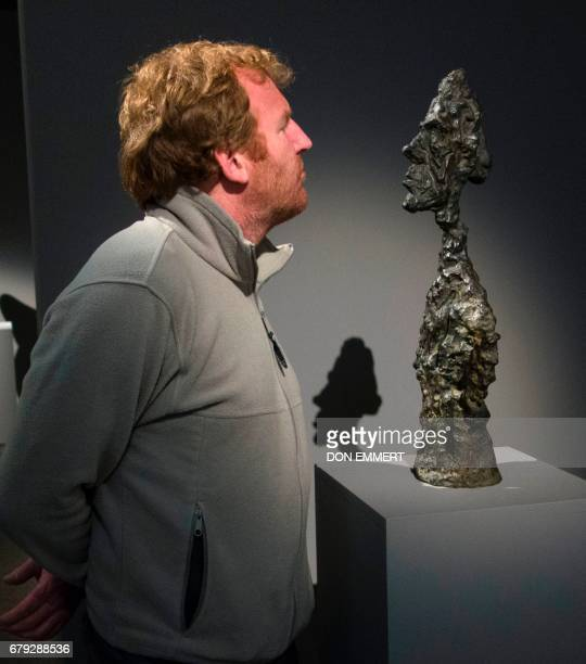 A journalist looks at 'Buste de Diego' by Alberto Giacometti during a media preview May 5 2017 at Sotheby's In New York The piece is one of the...