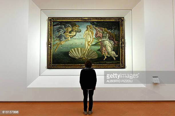A journalist looks at 'The birth of Venus' painted in the mid 1480s by Italian painter Sandro Botticelli during a press preview for the reopening of...