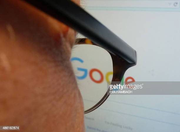 A journalist looks at the new Google logo at his work station in Washington DC on September 1 2015 Google on Tuesday refreshed its logo to better...