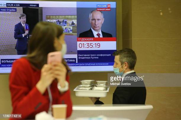 Journalist looks at the television screen in the hall prior to Vladimir Putin's annual press conference, on December 2020, in Moscow, Russia. This...