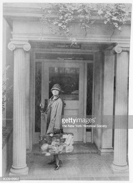 Journalist Mabel Herbert Urner in cloche hat standing on pillared stoop of her house holding suitcase covered with travel stickers New York New York...