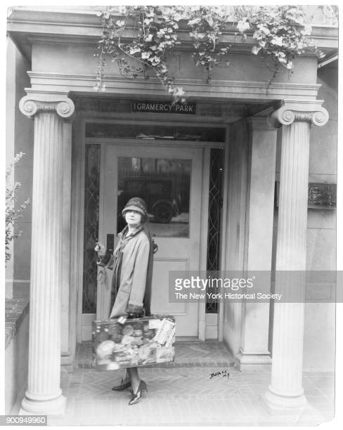 Journalist Mabel Herbert Urner in cloche hat standing on pillared stoop of her 1 Gramercy Park house holding suitcase covered with travel stickers...