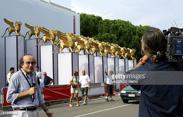 TV journalist makes a report as he stands across the 60 big Golden Lions of the Cinema palace at Venice Lido 31 August 2004 US diector Steven...