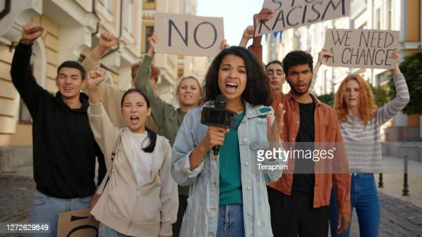 journalist makes live stream report at camera in front of multiracial protest at city street - campaigner stock pictures, royalty-free photos & images