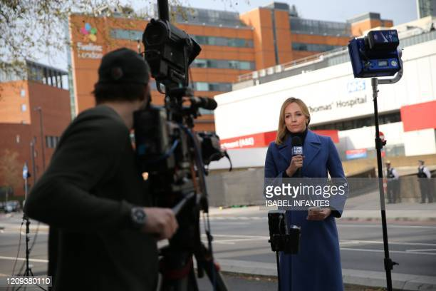 Journalist makes their report from outside St Thomas' Hospital in central London on April 8, 2020 where Britain's prime minister began a third day in...