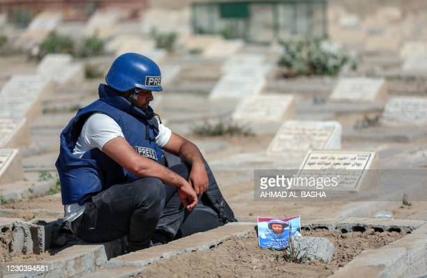 Journalist mourns by the grave of TV reporter Adib al-Janani who was killed in an attack on Aden airport, after his funeral procession in Yemen's...