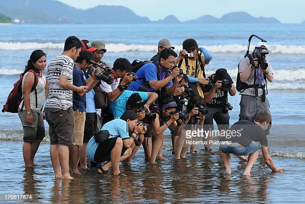 Journalist photograph Oscar Pujol Munoz, Spanis rider from Polygon Sweet Nice Cycling Team when released baby sea turtles in Air Manis Beach, Padang,...