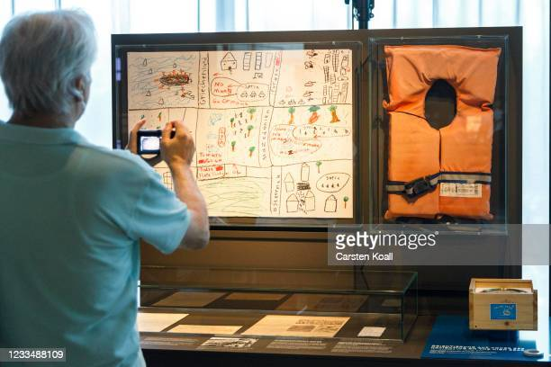 """Journalist photographs children's drawings next to a life jacket in the """"Routes and Campes"""" section in the new Documentation Center for Displacement,..."""