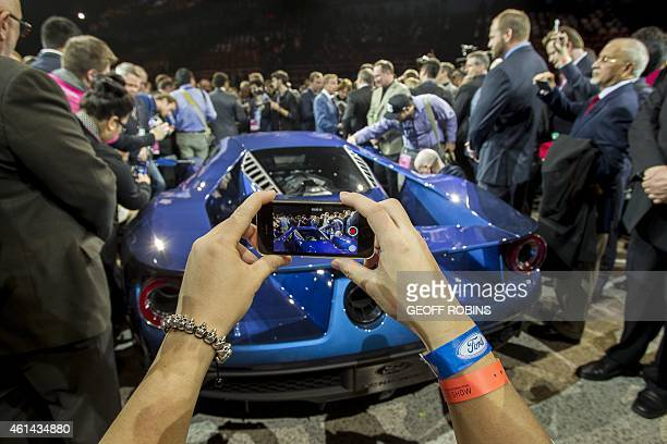 Journalist photographs the new Ford GT during the Ford Press conference at the 2015 North American International Auto Show in Detroit, Michigan,...