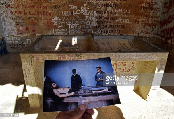 A journalist places in Vallegrande Bolivia on September 30 2017 a copy of a picture taken on October 10 1967 by AFP journalist Marc Hutten of the...