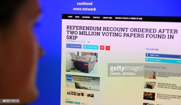 A journalist poses reading a satirical fake news story on the Southend News Network website in London on March 31 2017 The rise of fake news has been...