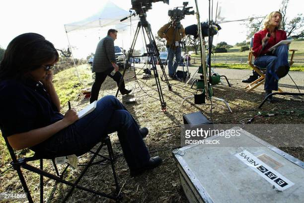 Journalist prepare their reports outside the entrance to pop star Michael Jackson's estate, known as Neverland Ranch, 19 November 2003, in Los...
