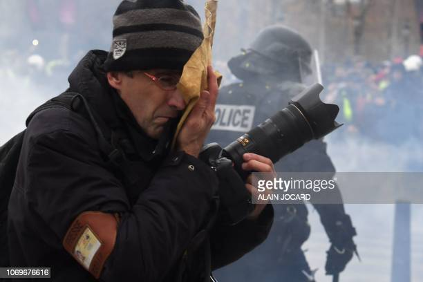 A journalist reacts amid tear gas smoke on the Champs Elysees avenue in Paris on December 8 2018 during a protest of Yellow vests against rising...