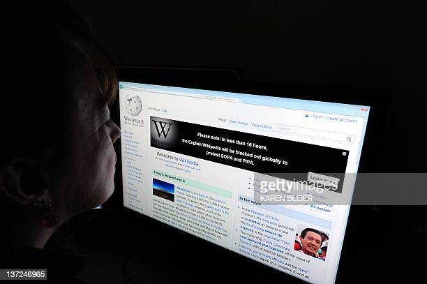 A journalist reads information on the online encyclopedia Wikipedia on Jauary 17 2012 in Washington DC Free online knowledge site Wikipedia will shut...