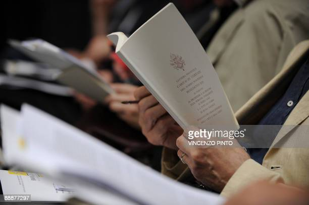 """Journalist reads Pope Benedict XVI's latest encyclical """"Caritas in Veritae"""" during a press conference for the release of the book on July 7, 2009 at..."""