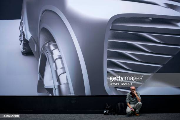 A journalist rests next to a poster during the press preview at the 2018 North American International Auto Show in Detroit Michigan on January 16...