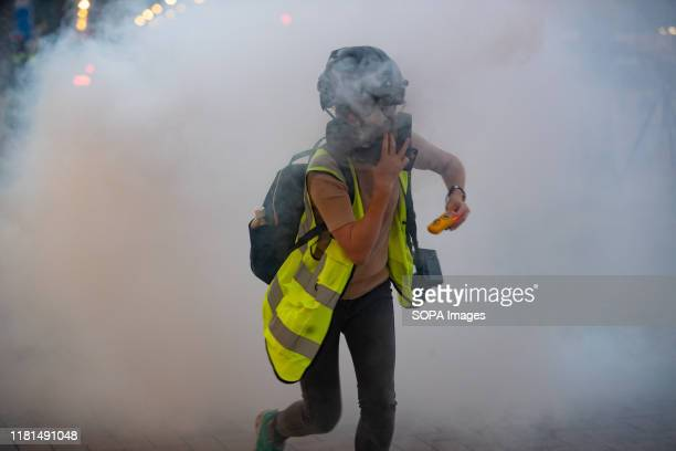 A journalist runs away from the teargas smoke during the demonstration Protests marked the 5th consecutive month of the Hong Kong uprising which was...