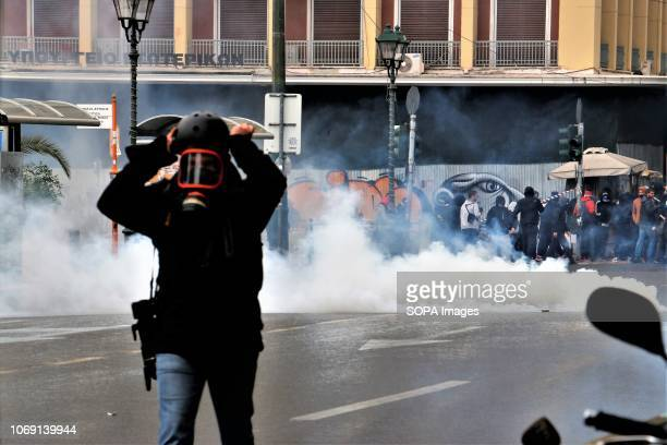 A journalist seen putting on a tear gas mask during the protest Students Demonstrated to mark the 10th anniversary of the murder of Alexandros...