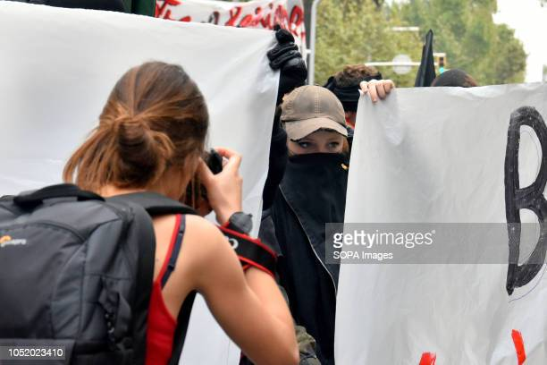 A journalist seen taking a picture of an antifascist protester with her face covered by a handkerchief during an antifascist protest against...