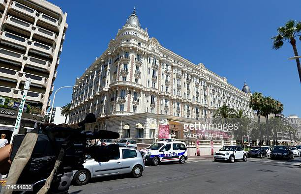 A journalist shhots with a camera outside the Carlton Hotel on July 28 2013 in the French Riviera resort of Cannes while French policemen investigate...