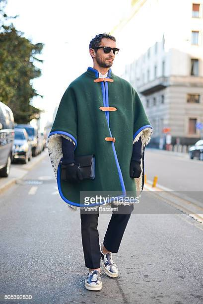 Journalist Simone Marchetti poses wearing a Loewe cape after the Vivienne Westwood show during the Milan Men's Fashion Week Fall/Winter 2016/17 on...