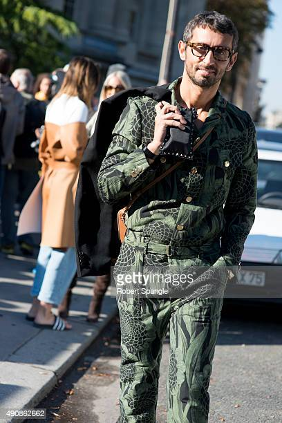 Journalist Simone Marchetti wears green and black floral print jumpsuit from Christian Pellizzari with blue blazer and black studded Valentino clutch...